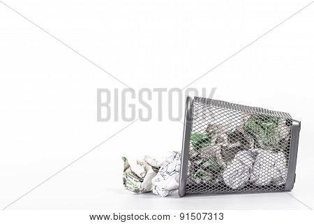 isolated fallen wastebasket full of waste paper