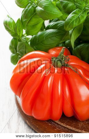 Fresh tomato with basil om old wooden board.
