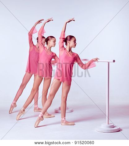 Three young ballerinas stretching on the bar on beige background poster