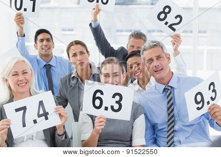 Smiling interview panel holding score cards in bright office