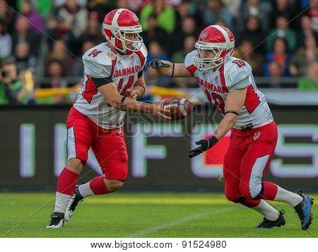 GRAZ, AUSTRIA - MAY 31, 2014: QB Kasper Skyum Jensen (#14 Denmark) hands off the ball to RB Lars Hyrsting Larsen (#18 Denmark) in match against Austria during the EFAF European Championships 2014 in Austria.