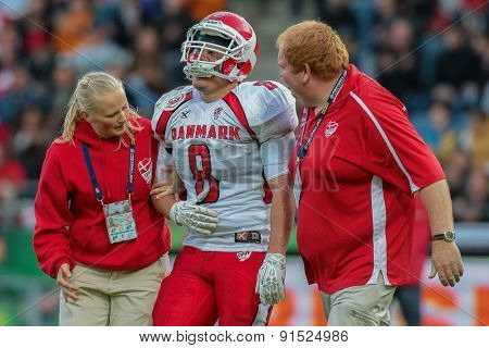 GRAZ, AUSTRIA - MAY 31, 2014: LB Mikkel Vangsgard (#8 Denmark) is led off the field after an injury in match against Austria during the EFAF European Championships 2014 in Austria..