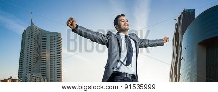 Successful Businessman With His Arms Wide Open. Joyous Man  With Success Perspective, Modern Buildin