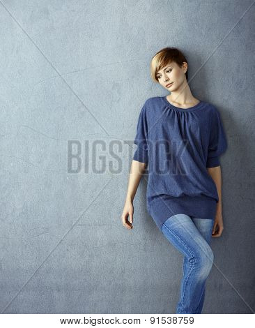 Attractive young woman leaning to wall daydreaming
