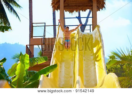 Excited Man Having Fun On Water Slide In Tropical Aqua Park