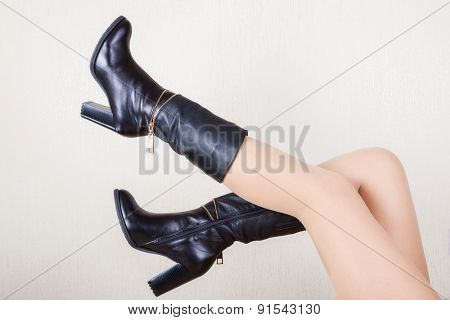 a pair of stylish boots on beautiful female legs.