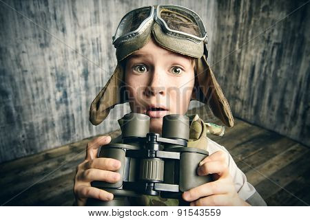 Boy plays the pilot, holding binoculars and surprised. Childhood. Fantasy, imagination.