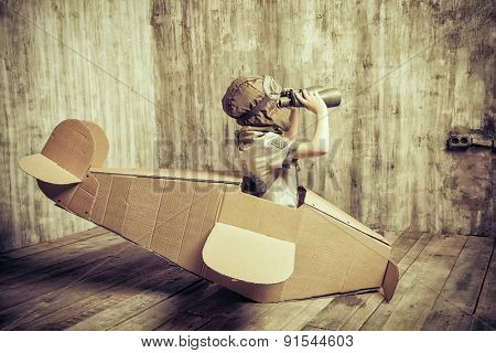 Cute dreamer boy playing with a cardboard airplane. Childhood. Fantasy, imagination. Retro style.
