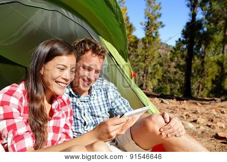Camping couple in tent using smartphone or small tablet looking at pictures photos. Campers smiling happy outdoors in forest. Happy multiracial couple having fun outdoor. Asian woman, Caucasian man