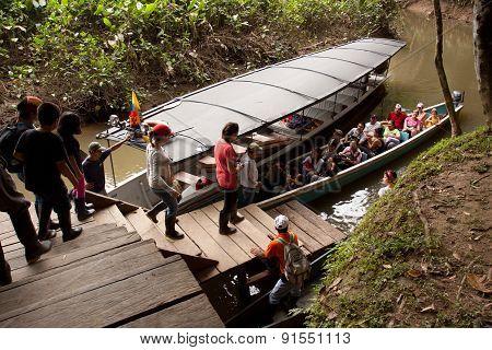 Unidentified tourists boarding a canoe in the amazon rainforest, Yasuni National Park, Ecuador