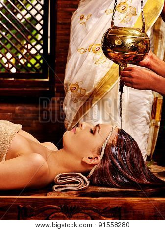 Young woman having head treatment with pouring oil in Ayurveda spa .