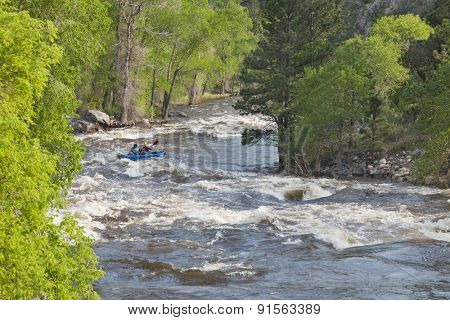 Springtime whitewater of Cache la Poudre River near Fort Collins, Colorado with a kayak in the middle of a rapid