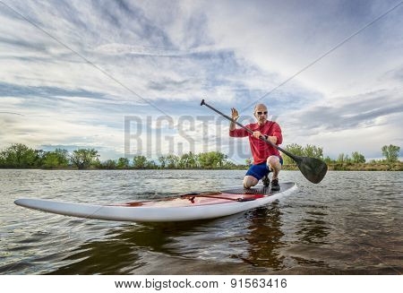 senior SUP paddler keneeling on his paddleboard, springtime lake scenry in Colorado