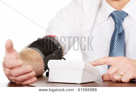 Closeup on businessman measuring blood pressure.