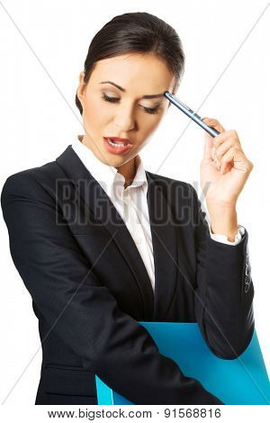 Thoughtful businesswoman holding a pen.