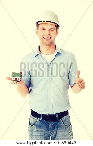 A forewoman holding a model house in hand and gesturing OK