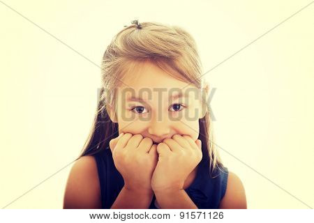 Scared little girl biting her nails