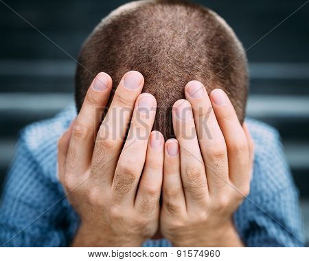 Closeup Portrait Of Despaired Young Man Covering His Face With Hands. Selective Focus On Hands