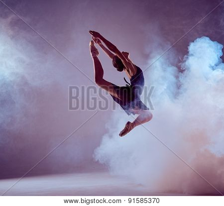 Beautiful young ballet dancer jumping on a lilac background.