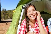 Camping woman applying sunscreen sun cream sunblock suntan lotion in tent smiling happy outdoors in forest. Happy biracial Asian Caucasian girl living healthy active lifestyle. poster