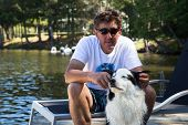 Dog enjoying attention from has owner on the cottage dock at the lakehouse poster