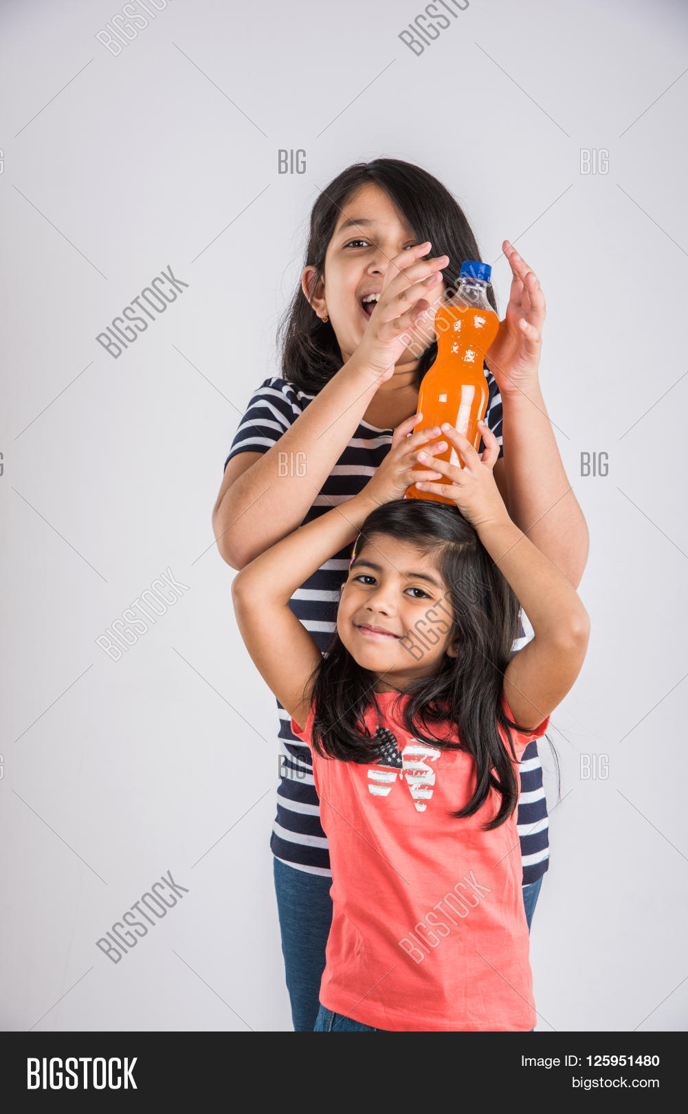two indian girls with cold drink bottle, two asian girls posing with cold  drink in