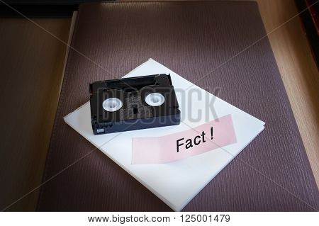 Mini DV cassette tape on note text word fact in dim light room background with copy space