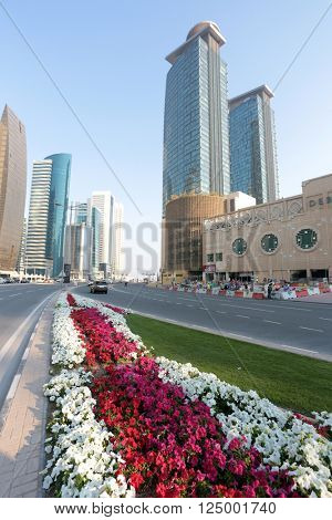 DOHA, QATAR - FEBRUARY 17, 2016: Municipal flowerbeds beside the City Centre mall and hotels in Dafna, with labourers are hard at work.