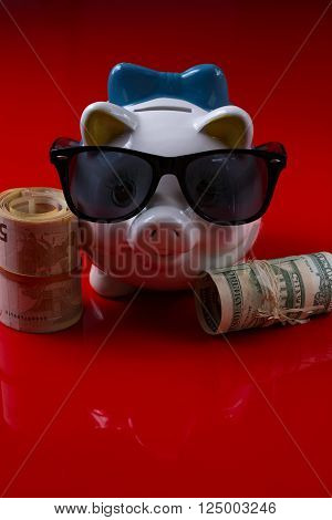 Piggy bank with black sunglasses and rolls cash on red background