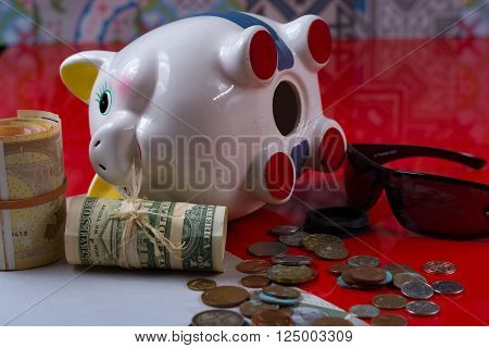 Opened piggy bank with black sunglasses and rolls cash on red background
