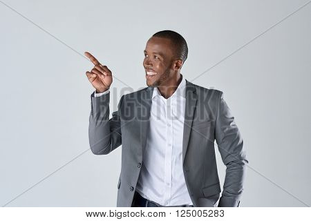 Charming handsome young black business man pointing his hand up to show present sell product