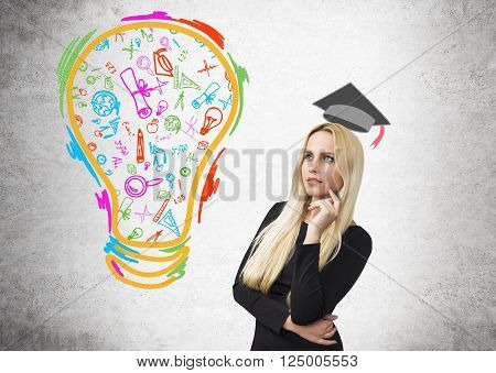 Businesswoman with hand at cheek, academic hat drawn over her, coloured bulb in left. Concrete background. Concept of education.