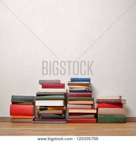 Severel stacks of old books on wooden floor