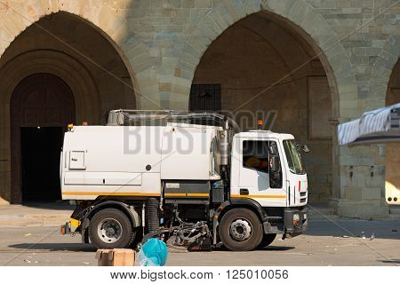 A truck (street sweeper machine) cleans the square after a street market in Pistoia, Tuscany, Italy poster