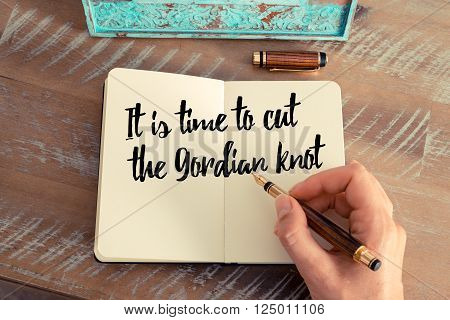 Retro effect and toned image of a woman hand writing on a notebook. Handwritten quote It is time to cut the Gordian knot as inspirational concept image