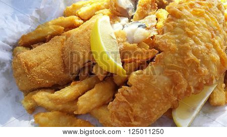 Closeup of flash fried fish and chips with lemon slice