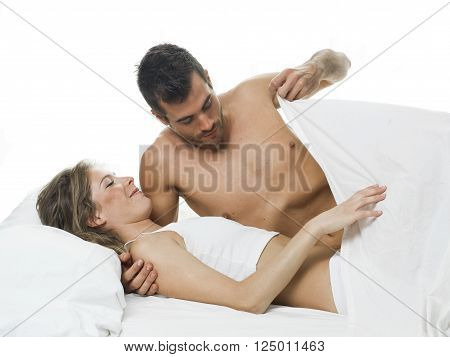 a man watching under the bed sheets before having sex with his woman