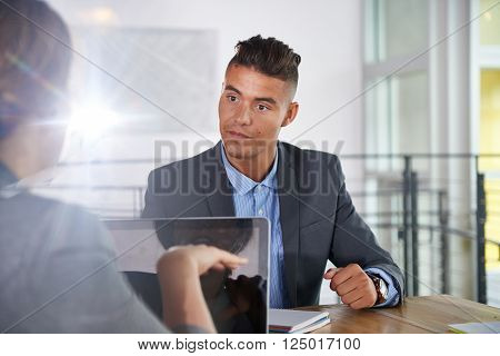 Candid photo of a corporate businesspeople group discussing strategies in professionnal indoors setting. ** Note: Shallow depth of field