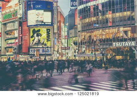 TOKYO, JAPAN - APRIL 04, 2016: Pedestrians walk at Shibuya Crossing during the holiday season. The scramble crosswalk is one of the largest in the world.