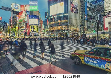 TOKYO JAPAN - APRIL 04 2016: Pedestrians walk at Shibuya Crossing during the holiday season. The scramble crosswalk is one of the largest in the world.