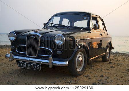 HIKKADUWA, SRI LANKA - MARCH 24, 15: The car Wolseley 1500 on the Indian ocean in the evening twilight. Rare model retro car