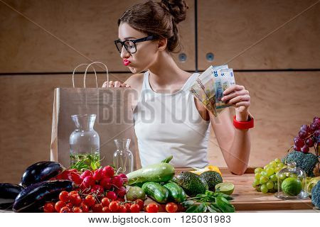 Dispirited young woman looking to the bag holding money for buying expensive natural food. High price of healthy natural food