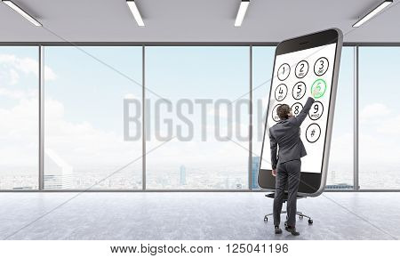 Businessman touching huge smartphone model in empty office. Panoramic window city view. Concept of presentation.