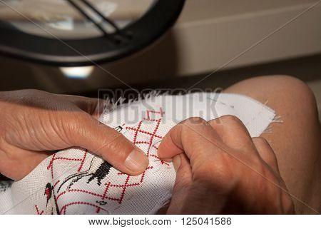 Woman's hands skillfully embroider on canvas, handmade, Ukraine