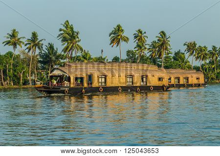 KERALA BACKWATERS INDIA - 1ST APRIL 2016: Traditional houseboats in the Kerala backwaters of south India during the day. People can be seen.