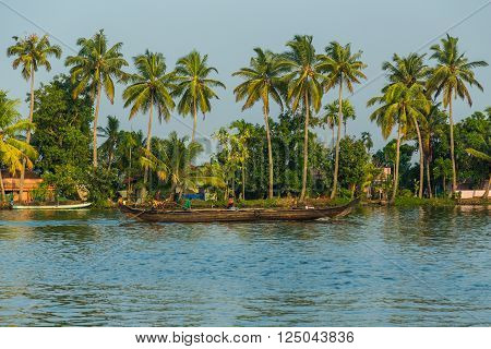 KERALA BACKWATERS INDIA - 1ST APRIL 2016: A boat in the Kerala backwaters of south India during the day. People can be seen.