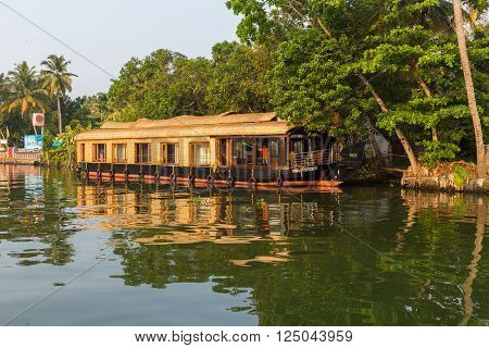 KERALA BACKWATERS INDIA - 2ND APRIL 2016: Traditional houseboats in the Kerala backwaters of south India during the day. People can be seen.