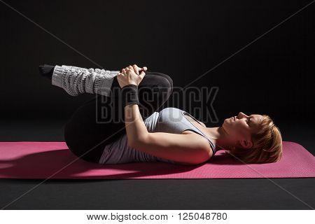 Young woman practicing yoga, Pawanmuktasana / Wind Relieving pose