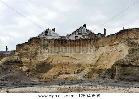 Homes on the cliff edge at Happisburgh in Norfolk demonstrating levels of erosion along the East Coast. poster