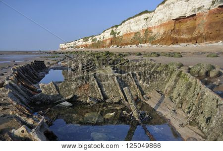 The cliffs beach and shipwreck remains on the beach at Hunstanton in Norfolk UK.